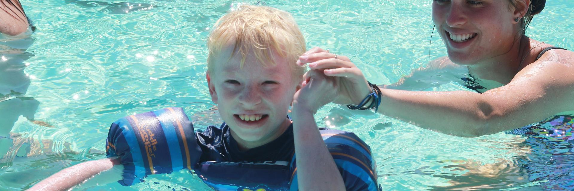 Boy smiling. enjoying the pool.
