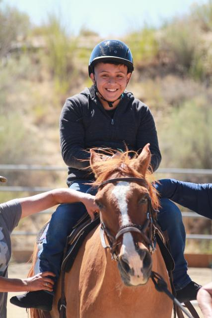 Boy enjoying horseback riding.