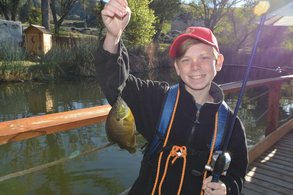 Boy happily holding fish.