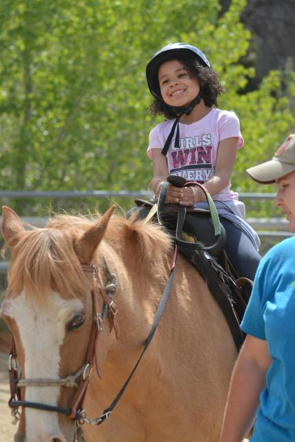Girl enjoying horseback riding.